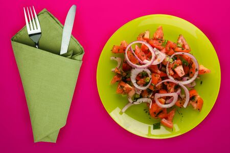 Vegetarian food. tomatoes, onions, dill on a green plate on a red background. healthy food