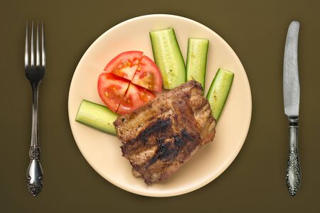 fried pork ribs with chopped cucumbers and tomatoes on a beige plate. pork ribs on an brown green background. grilled ribs top view