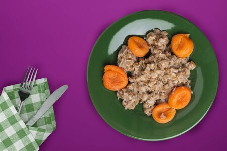muesli on a green plate on a purple background. granola with fruits dried apricots on a plate top view. healthy eating. healthy breakfast. vegetarian food