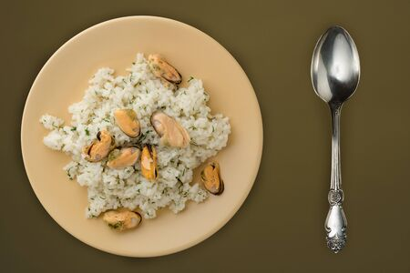White rice with mussels on a beige plate. Rice with mussels on a brown green background. rice top view.asian food Banco de Imagens