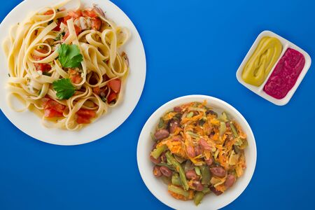 spaghetti on a white plate with vegetable salad top view. spaghetti tomatoes, onions, cabbage on a blue  background. healthy food flat lay