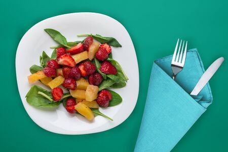 Vegetarian food top view. healthy food. spinach salad, apricot, strawberries on a white plate on the turquoise  background. Stock Photo