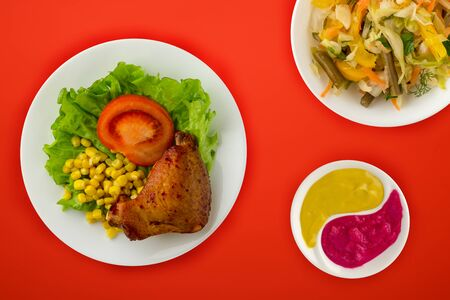 chicken wing with lettuce, corn and tomatoes on a white plate. chicken wing with vegetable salad and sauce on a red  background top view