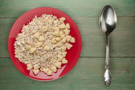muesli on a red  plate on a green  wooden background.muesli on a plate top view. healthy eating. healthy breakfast. vegetarian food