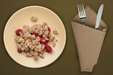 muesli on a beige plate on a green brown background. granola with fruits strawberry on a plate top view. healthy eating. healthy breakfast. vegetarian food