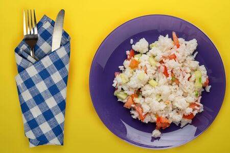 rice on a purple plate on a yellow background. white rice top view. Asian cuisine .vegetarian food