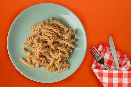 pasta on a light green plate in tomato sauce on a background of titanium color. Mediterranean food on an orange background. healthy food