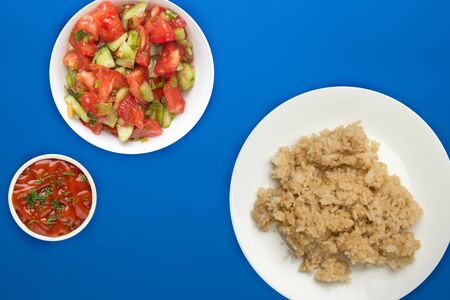 white rice in soy sauce on a white plate. rice with vegetable salad on a blue background top view. asian food