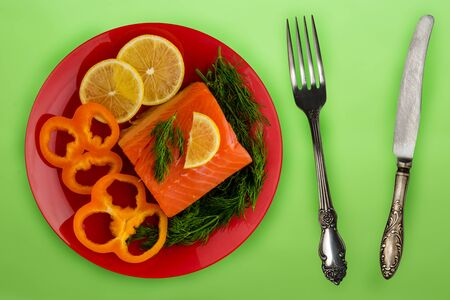 red fish with dill, pepper, lemon on a red  plate on the green background. sea food