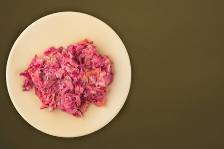 herring under a fur coat on a beige plate. Herring under a fur coat on a grenn brown  background. herring, beetroot, carrot, mayonnaise and onion salad top view.