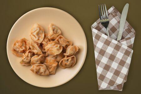dumplings on a beige plate against a brown green  background. Dumplings meat in tomato sauce top view. Asian cuisine