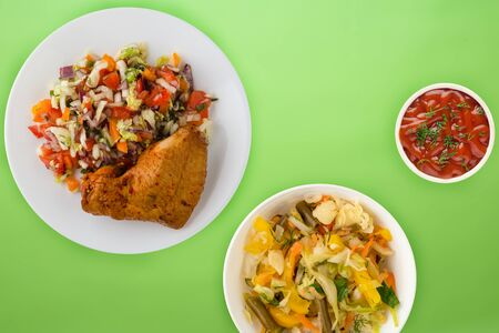 fried chicken thighs with vegetables on a white plate on the lime background. fast food with vegetable salad top view. unhealthy food.flat ley