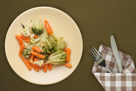 Provencal vegetables on a plate. fried vegetables on a beige  plate on a brown green background.broccoli and carrots on a plate top view. wholesome food