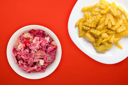 french fries on a white plate in the red  background. french fries with vegetable fish  salad fast food top view. unhealthy food