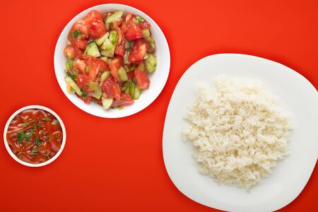 white rice on a white  plate. rice with vegetable salad  on a red  background top view .asian food