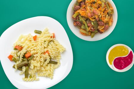 pasta on a white  plate with vegetables on a  green background. Mediterranean food on with vegetable salad and sauce. healthy food top view. flat lay