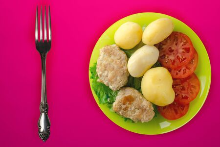 Cutlets with potatoes and stewed tomatoes. cutlet on a green plate on a red background background. rustic food top view Stock Photo