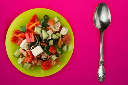Greek salad on a red background. Greek salad on a green plate top view. healthy vegan food Stock Photo