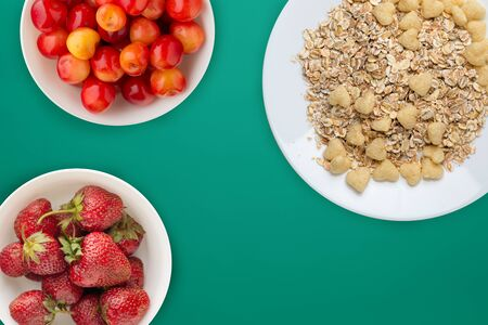 granola on a white plate on green background.muesli with fruit on a plate top view. healthy eating. Healthy breakfast. Vegetarian food