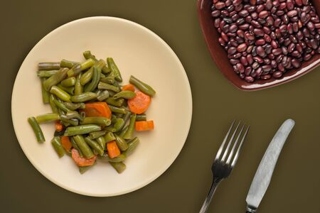Green beans with garlic carrots on a beige plate on a brown green background.green beans with carrots top view. healthy vegan food. Stock Photo
