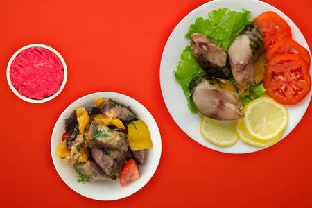 sliced mackerel with lettuce, tomatoes and lemon on a white plate with vegetable salad on a red background. sliced mackerel with vegetables on a plate top view. seafood flat lay