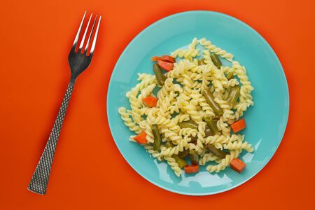 pasta on a cyan plate with vegetables on a background of titanium color. Mediterranean food on an orange background. healthy food