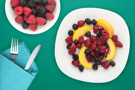 dietary, healthy food. blackberry, raspberry, nectarine on a white plate on a plate. Vegetarian food on a green background top view.