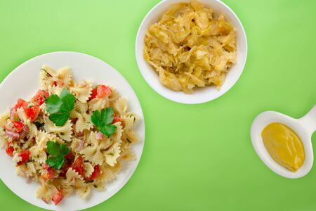 pasta on a white plate with vegetables. Mediterranean food with vegetable salad and sauce on the lime background. healthy food falt lay