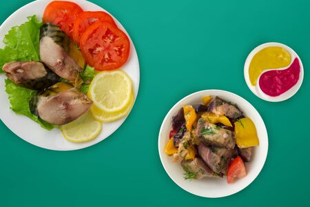 sliced mackerel with lettuce, tomatoes and lemon on a white plate with vegetable salad on a green background. sliced mackerel with vegetables on a plate top view. seafood flat lay