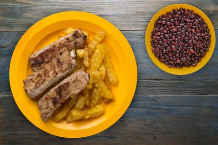 pork ribs and french fries on a yellow plate on a blue wooden background.fast food top view.junk food