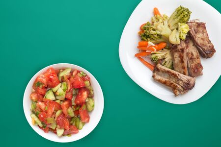 fried pork ribs with broccoli, carrots and garlic on a white plate. fried pork ribs with vegetable salad on a green background. hearty rustic food top view.flat lay