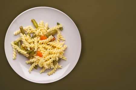 pasta on a light gray plate with vegetables on a background green brown color. Mediterranean food on an green background top view. healthy food