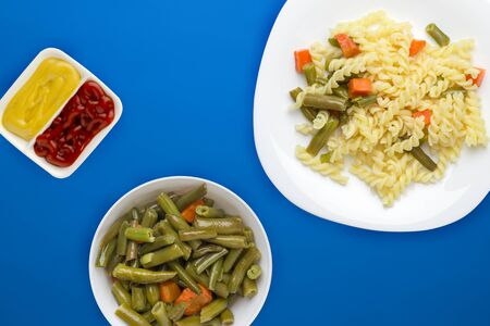 pasta on a white  plate with vegetables on a blue background. Mediterranean food on with vegetable salad and sauce. healthy food top view. flat lay