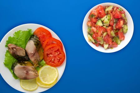 sliced mackerel with lettuce, tomatoes and lemon on a white plate with vegetable salad on a blue background. sliced mackerel with vegetables on a plate top view. seafood flat lay