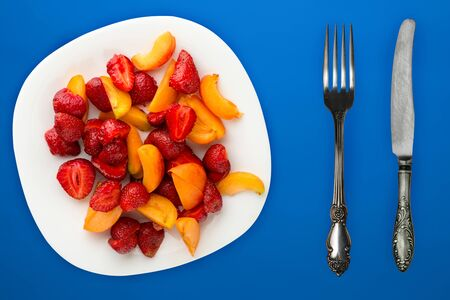 healthy food. Strawberries and apricots on a white plate. fresh fruits on a  blue background top view.