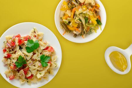 pasta on a white plate with vegetables. Mediterranean food with vegetable salad and sauce on the yellow background. healthy food falt lay