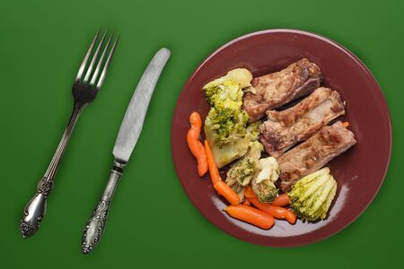 fried pork ribs with broccoli, carrots and garlic on a brown plate. fried pork ribs with vegetables against a dark green background. hearty rustic food top view Stock Photo