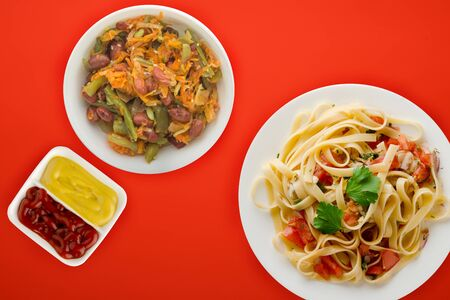 spaghetti on a white plate with vegetable salad top view. spaghetti tomatoes, onions, cabbage on a red background. healthy food flat lay Фото со стока