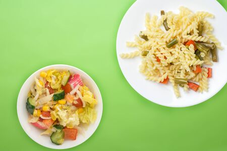 pasta on a white  plate with vegetables on a lime background. Mediterranean food on with vegetable salad and sauce. healthy food top view. flat lay