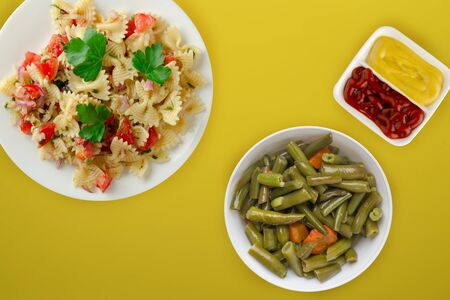 pasta on a white plate with vegetables. Mediterranean food with vegetable salad and sauce on the yellow background. healthy food falt lay Фото со стока - 134167185