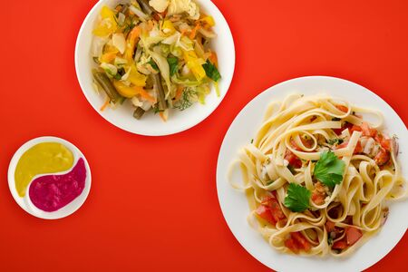 spaghetti on a white plate with vegetable salad top view. spaghetti tomatoes, onions, cabbage on a red background. healthy food flat lay Фото со стока - 134166983