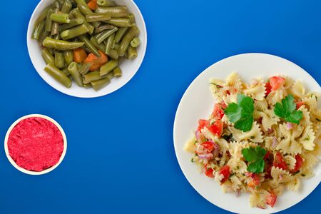 pasta on a white plate with vegetables. Mediterranean food with vegetable salad and sauce on the blue background. healthy food falt lay Фото со стока - 134166996