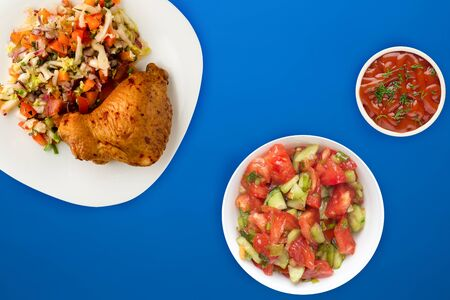 fried chicken thighs with vegetables on a white plate on the blue background. fast food with vegetable salad top view. unhealthy food.flat ley