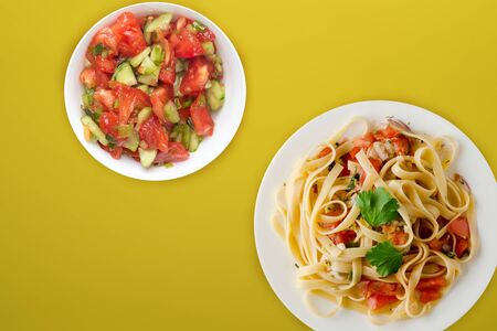 spaghetti on a white plate with vegetable salad top view. spaghetti tomatoes, onions, cabbage on a yellow background. healthy food flat lay Фото со стока - 134166673