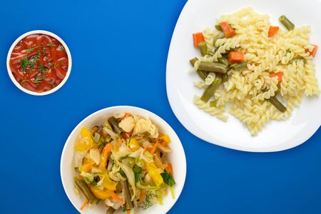 pasta on a white  plate with vegetables on a blue background. Mediterranean food on with vegetable salad and sauce. healthy food top view. flat lay Фото со стока - 134166550