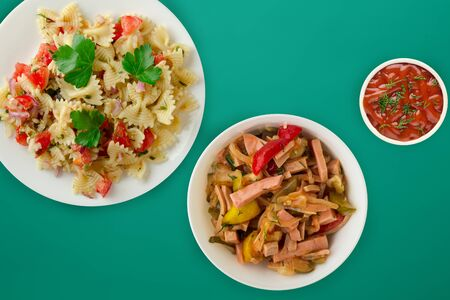 pasta on a white plate with vegetables. Mediterranean food with vegetable salad and sauce on the green  background. healthy food falt lay