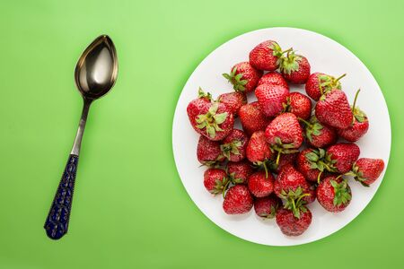 strawberries on a white plate top view. Strawberries on the lime background. Healthy food. vegan food.