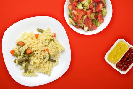 pasta on a white plate with vegetables on a red background. Mediterranean food on with vegetable salad and sauce. healthy food top view. flat lay Фото со стока