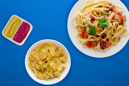 spaghetti on a white plate with vegetable salad top view. spaghetti tomatoes, onions, cabbage on a blue background. healthy food flat lay Фото со стока