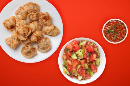 dumplings on a white plate against a red background. Dumplings meat in tomato sauce with vegetable salad top view. Asian cuisine Stock Photo